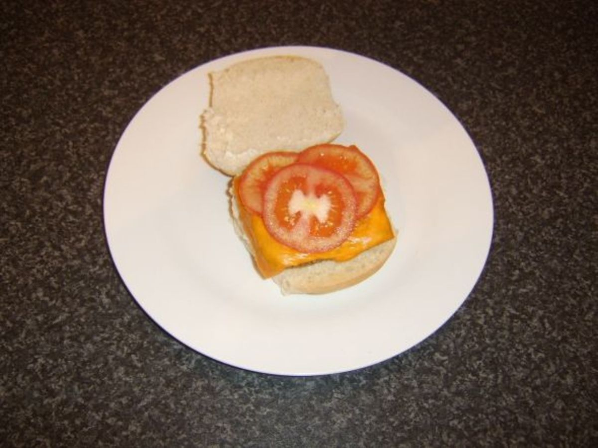 Roll and sausage with melted cheese and tomato