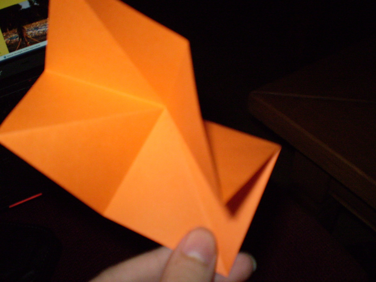 Hold a corner in your hand, and fold in one of the sides, as if you were folding edge to edge again.