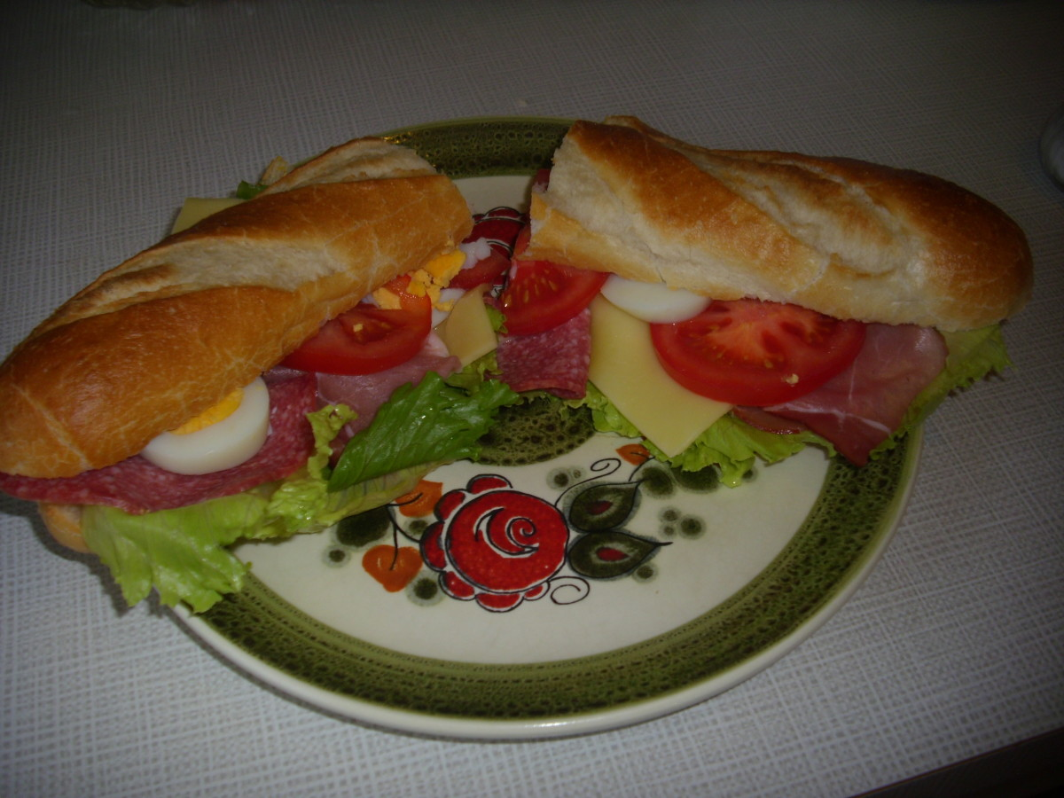 Salami, Cheese, Schwarzwälder (Black Forest Ham) baguette sandwich cut in the middle.