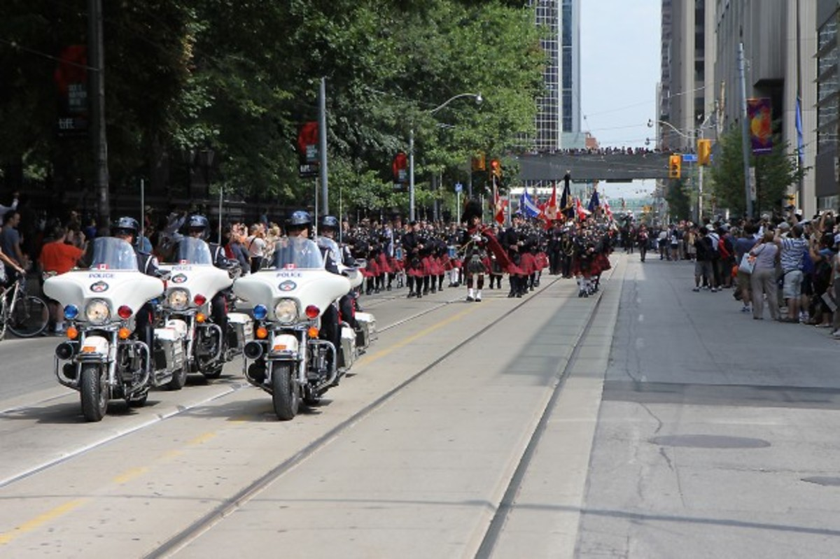 Police lead the procession down Queen Street.