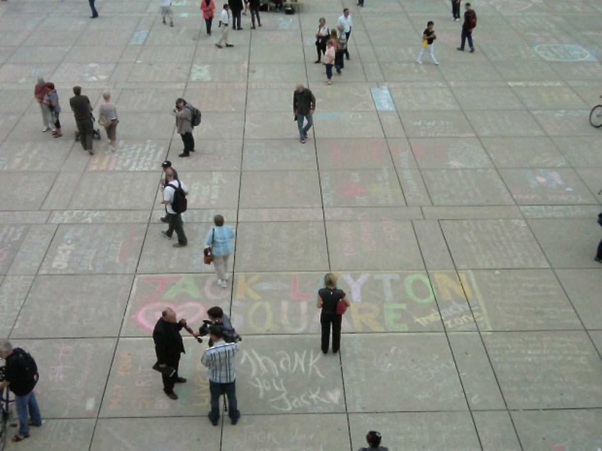 Messages in honour of Jack Layton written in chalk cover the pavement of Nathan Phillips Square in Toronto.