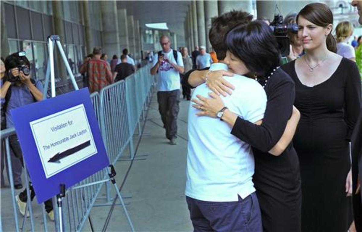 Olivia Chow hugs people standing in line to pay their respects.