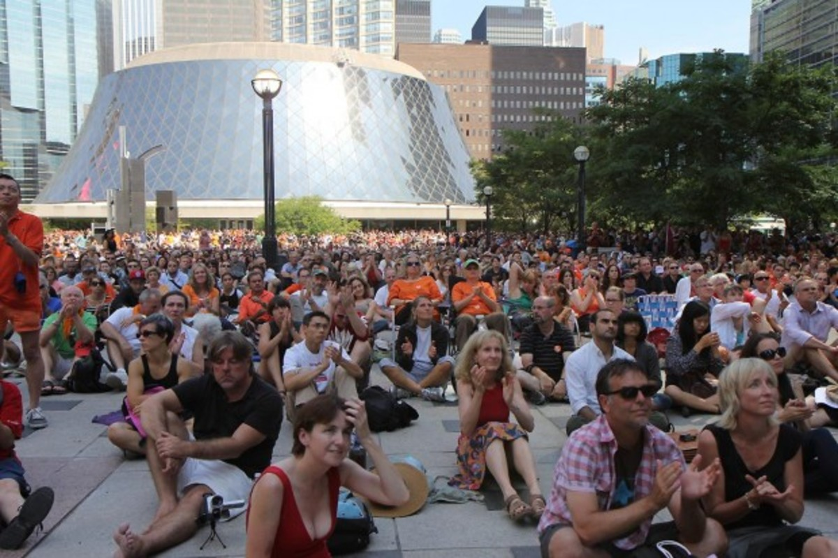 Crowds of people filled David Pecaut Square in downtown Toronto to watch the service on large television screens. Roy Thomson Hall, where Laytons funeral was held, is seen in the background.