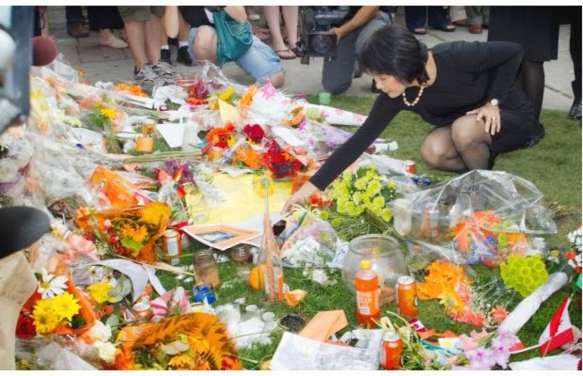 Olivia Chow looks over the memorial of flowers and notes left on Parliament Hill.