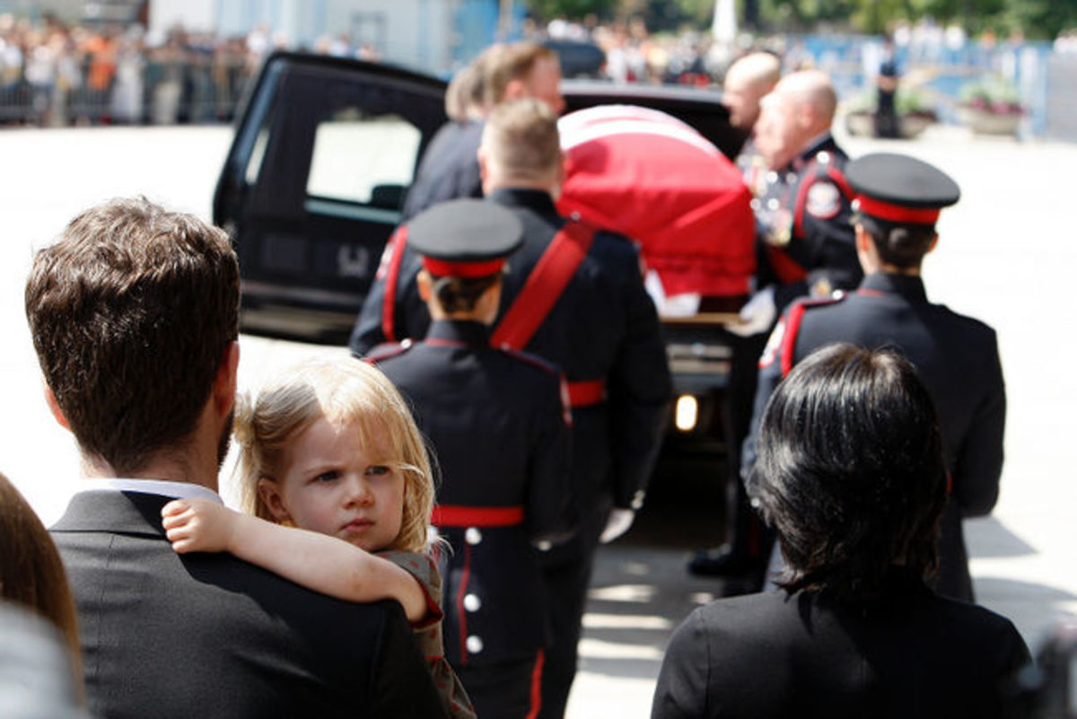 Sarah Layton's daughter Beatrice looks out as her granddad's casket is carried from city hall during the funeral for NDP Leader Jack Layton August 27, 2011.