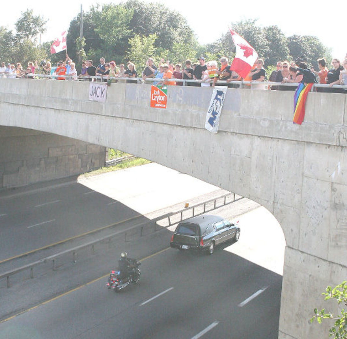 People wave Canadian flags and signs from an overpass as the hearse carrying Jack Layton's body passes along HWY 401 at Kingston, Ont., Thursday, Aug. 25, 2011.