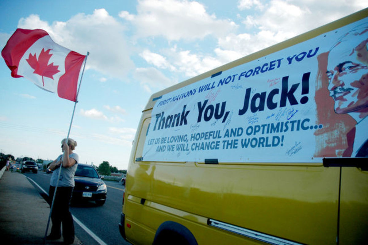 A Canadian flag is waved in Trenton, Ont., while waiting for Jack Layton's funeral motorcade to pass Thursday, Aug. 25, 2011.