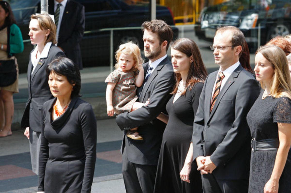 Olivia Chow walks towards Roy Thomson Hall in the funeral procession with Mike and Sarah Layton and their families, August 27, 2011.
