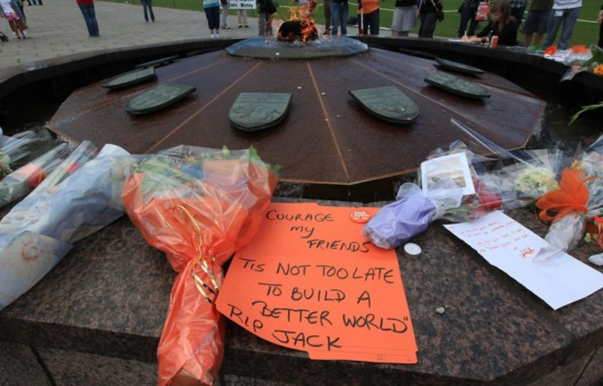 Mourners left floral tributes and notes, including this one featuring the words of former NDP leader Tommy Douglas, at the Centennial Flame in Ottawa.