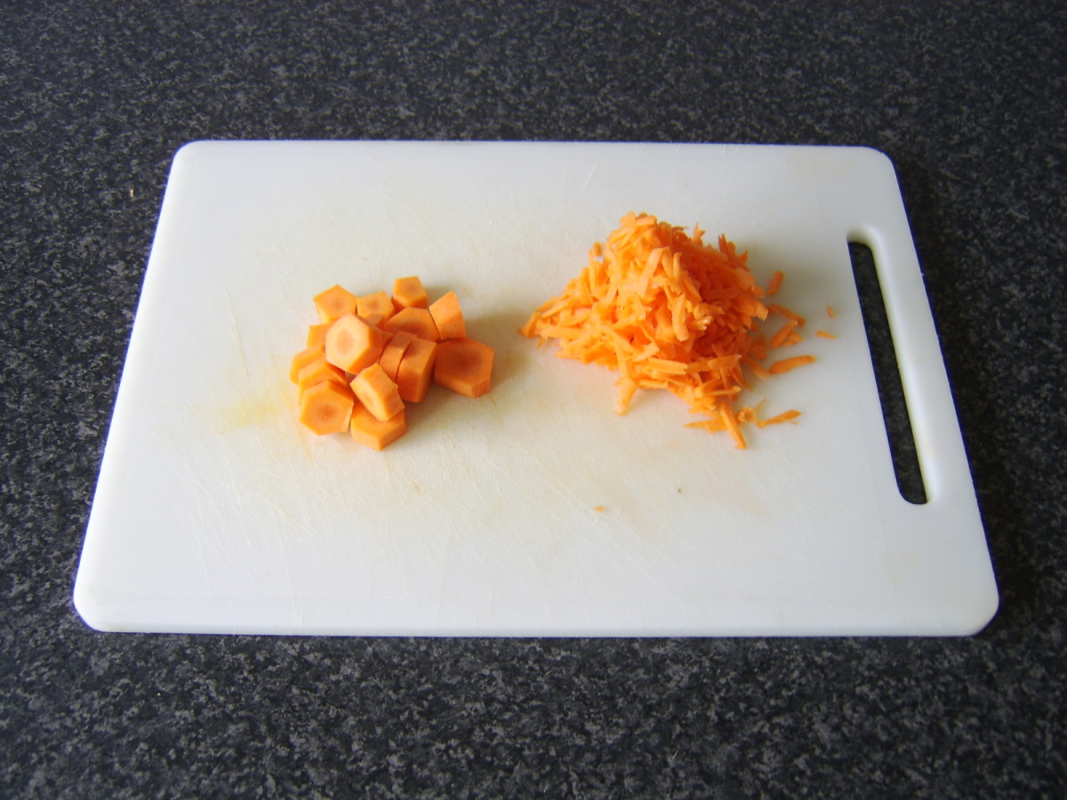 One carrot is grated and the other is sliced in to discs