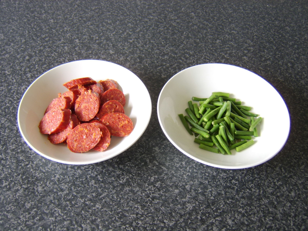 Chorizo and green beans are prepared for the soup