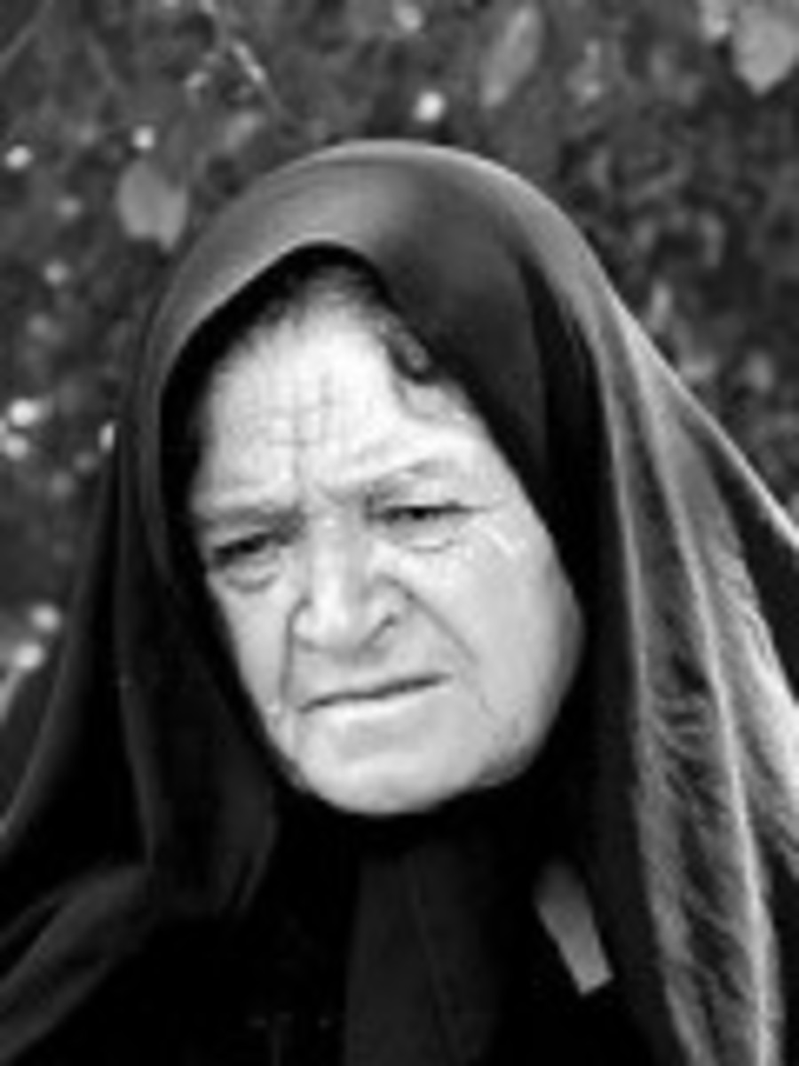 Sad, old Iranian woman wearing a black chador