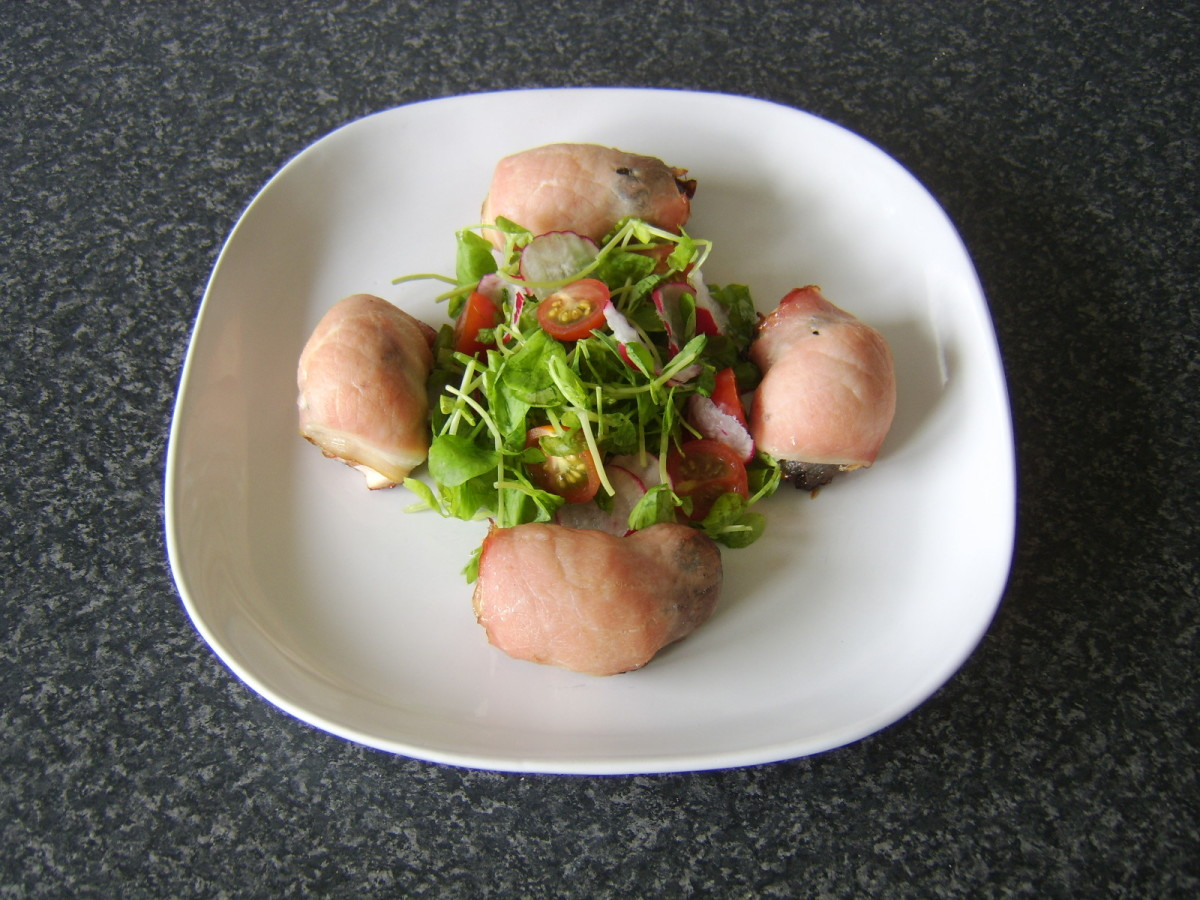 Chicken devils on horseback are arranged around the salad