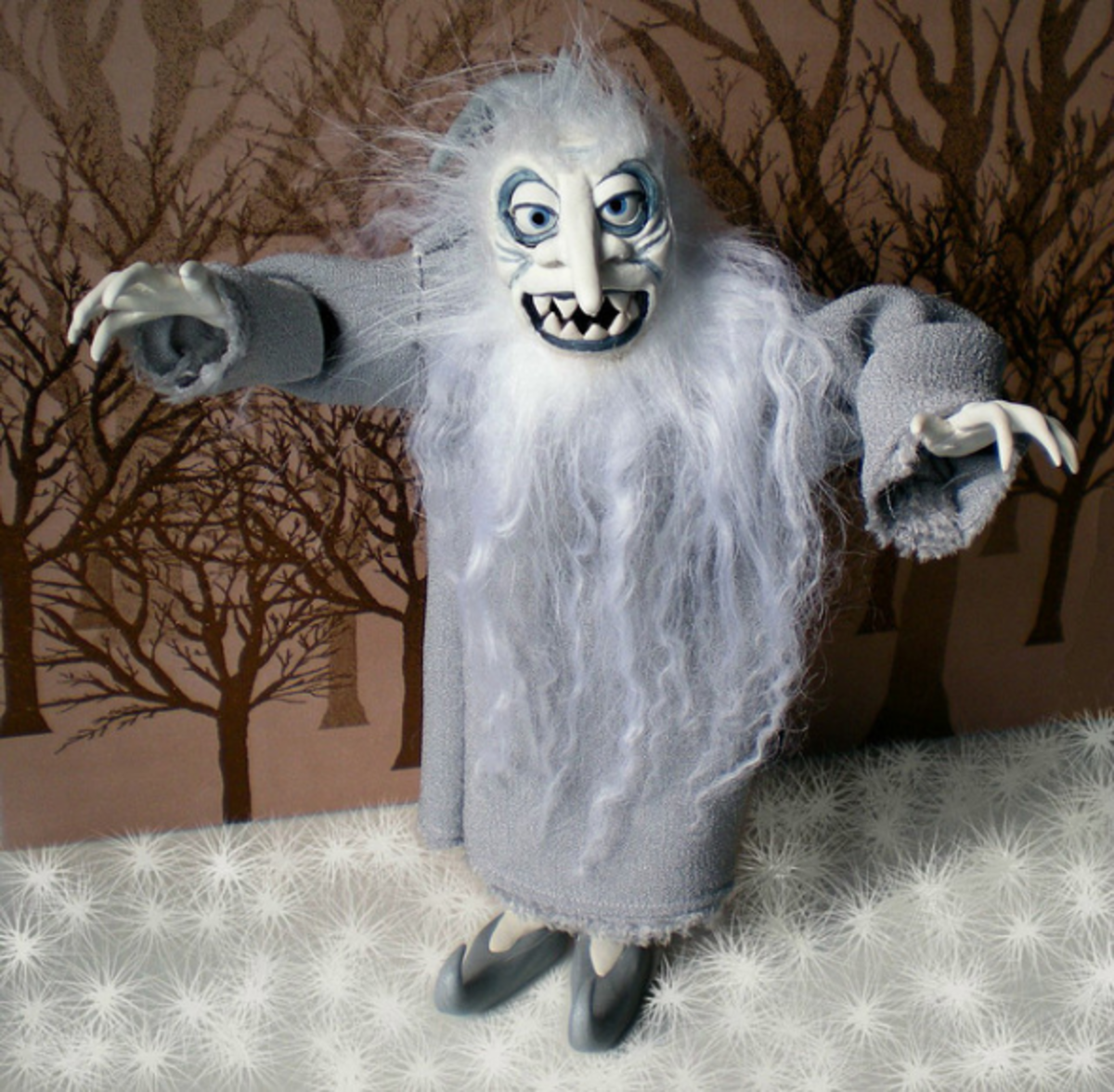 Winter Warlock is made of polymer clay with a foil and wire armature, and has been painted with acrylic paints. The hair is a mixture of Tibetan lambswool and polyester fur.