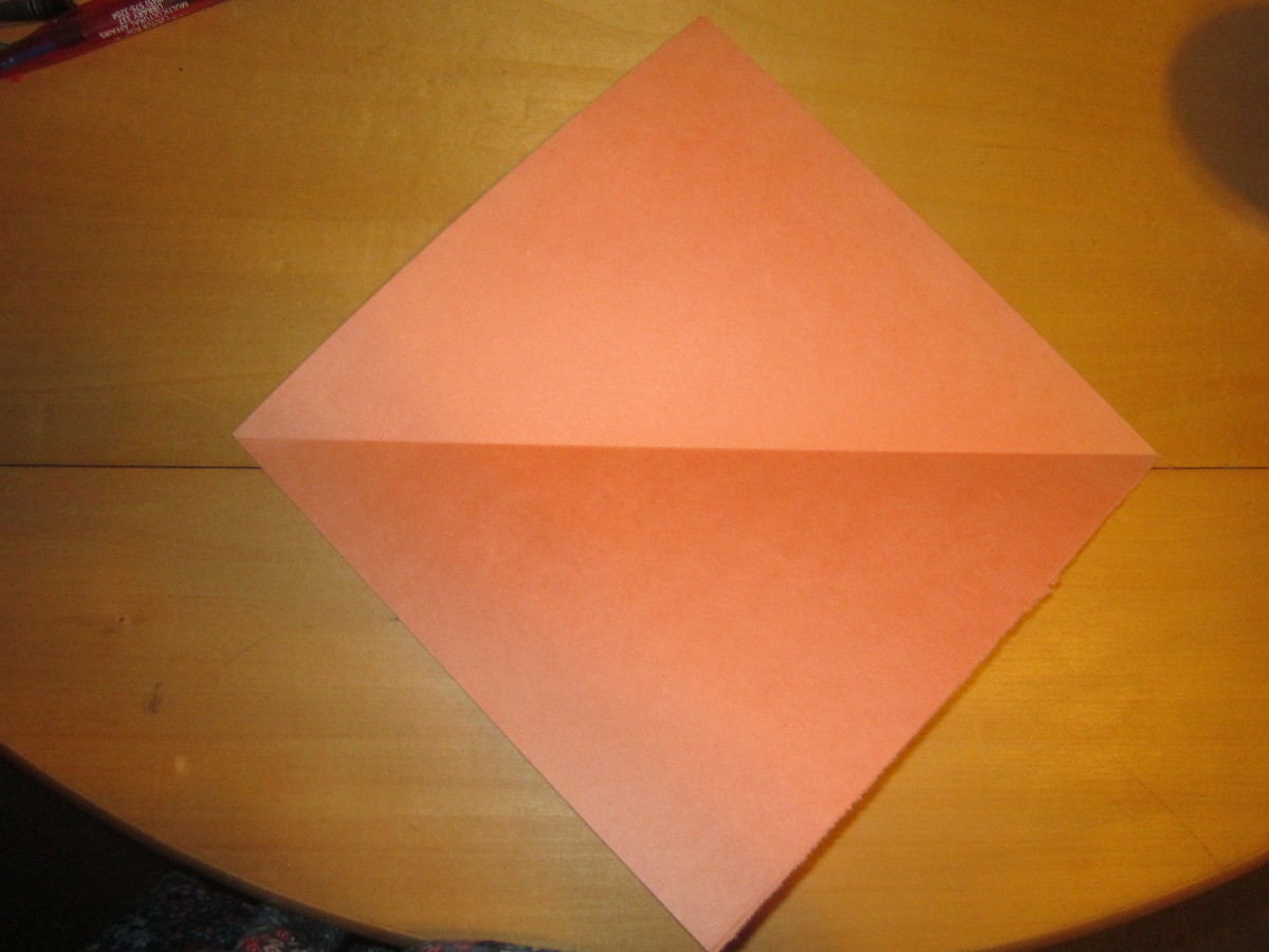 Start with a square sheet of paper.  If you don't have a square sheet trim excess off a rectangular sheet.  I would not advise using construction paper or heavy paper like I did because it doesn't stay flat after folding.