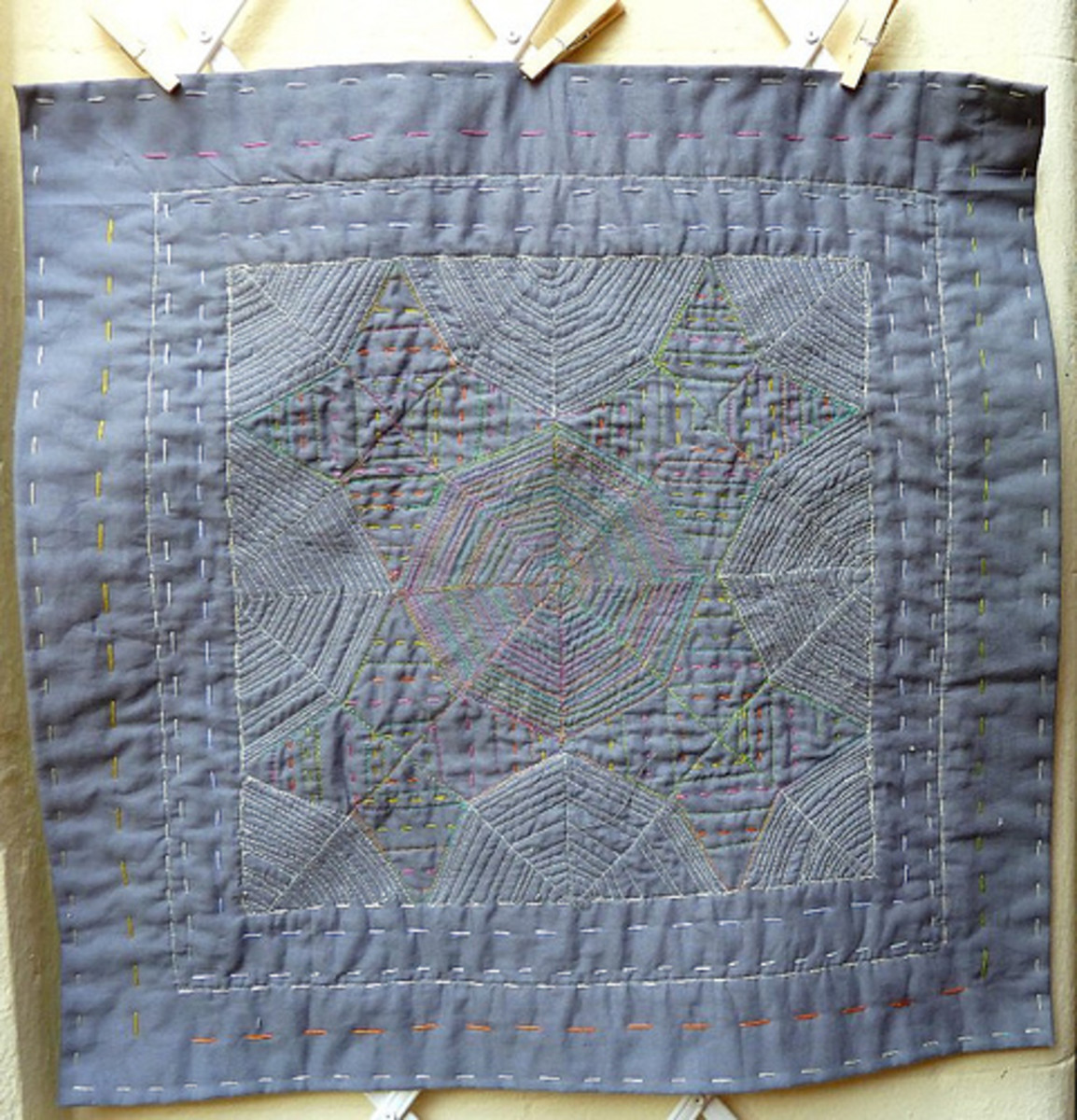 This is actually the back of a quilt that is not whole cloth, but the simple running stitches show that you do not need elaborate patterns or fabric to make a beautiful quilt.