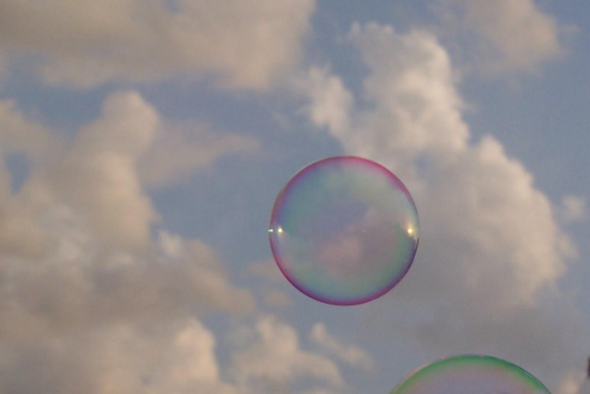 Colorful bubbles ascend above the clouds.