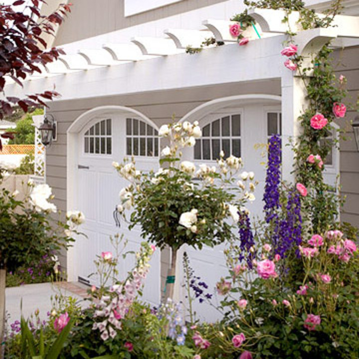classic Nantucket garage with the pergola and roses above the curved garage doors