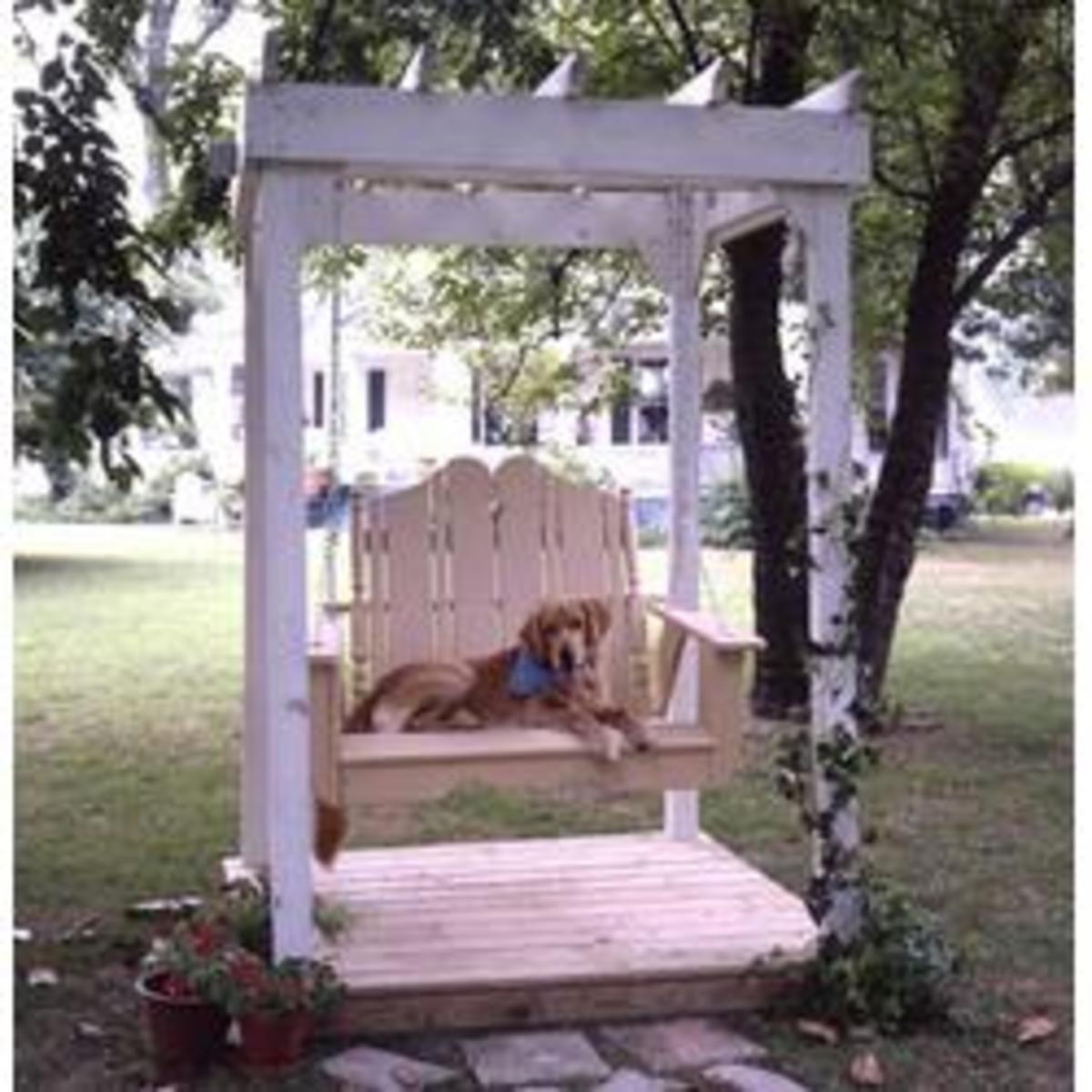 white and wood tones lend this pergola with a swing a little bit of both Victorian and Nantucket Inspired garden design inspiration