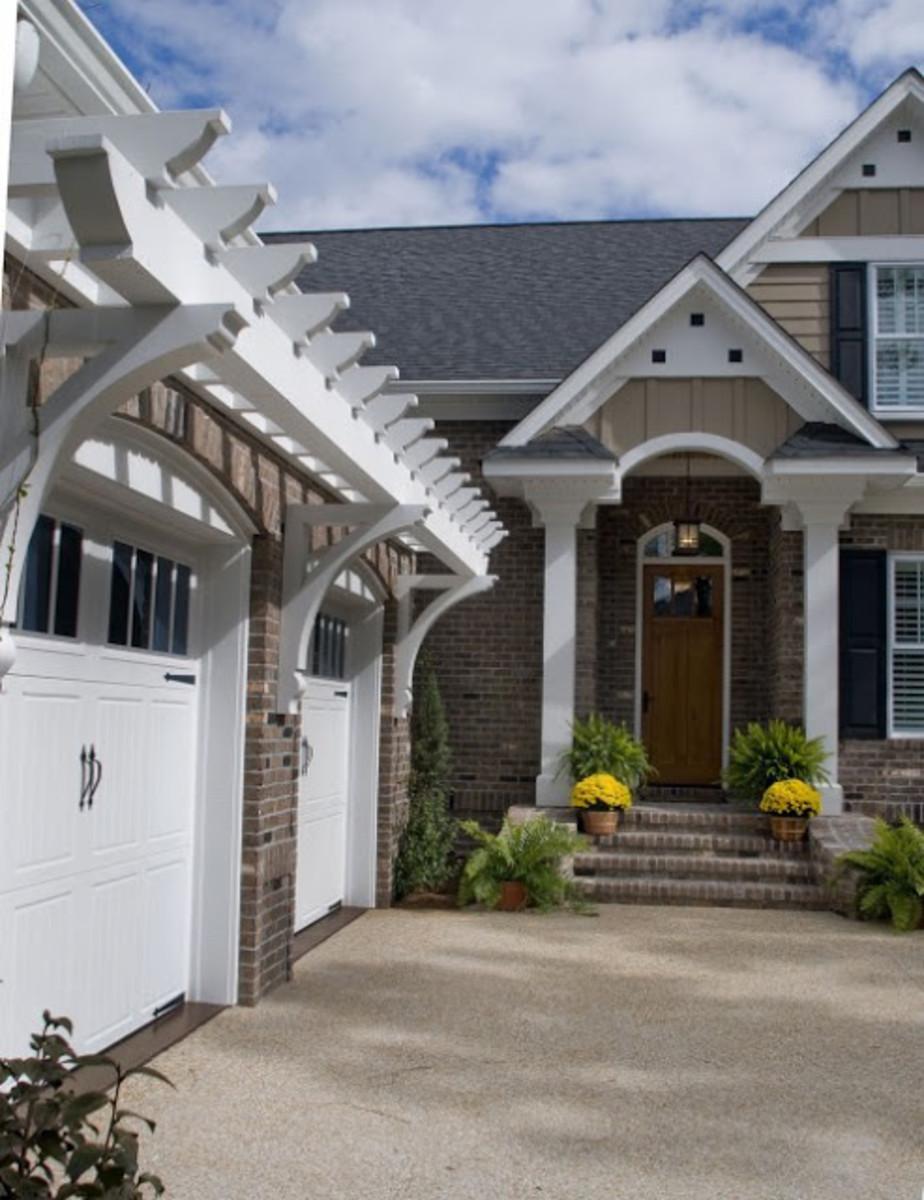 classic white Nantucket like pergola over white garage doors with windows