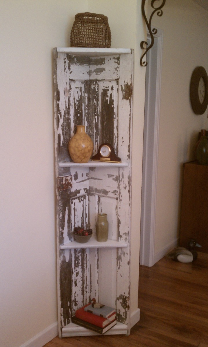 We created this great corner shelf out of an old door the paint was already beginning to flake so we helped it along with our sander leaving it heavily distressed and ready for the buyer to take home. Out total cost on this piece was less that $50.