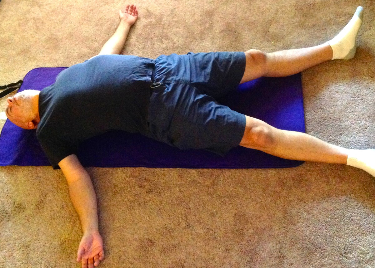 Restorative supine pose with rolled blanket along the spine.