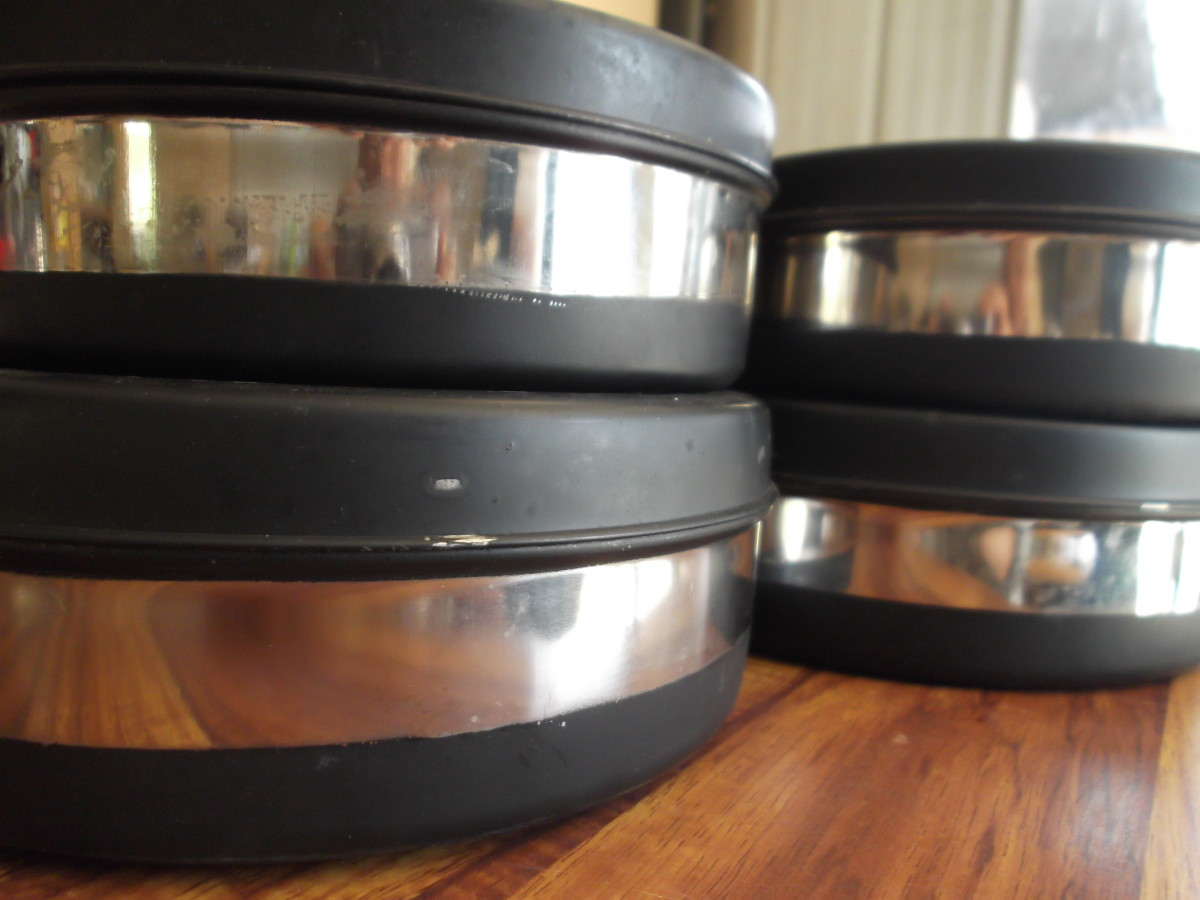 Black strips on the sides and totally black lid. Stainless steel inside. The cooking pans that came with our Tulsi solar oven are still in good condition years later. :)