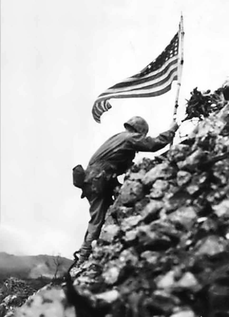 Lt. Col. Richard P. Ross commander of the 1st Battalion, 1st Marines braves sniper fire to place the divisions colors on a parapet of Shuri Castle on the 30th of May 1945. The flag was first raised over Cape Gloucester and then Peleliu.