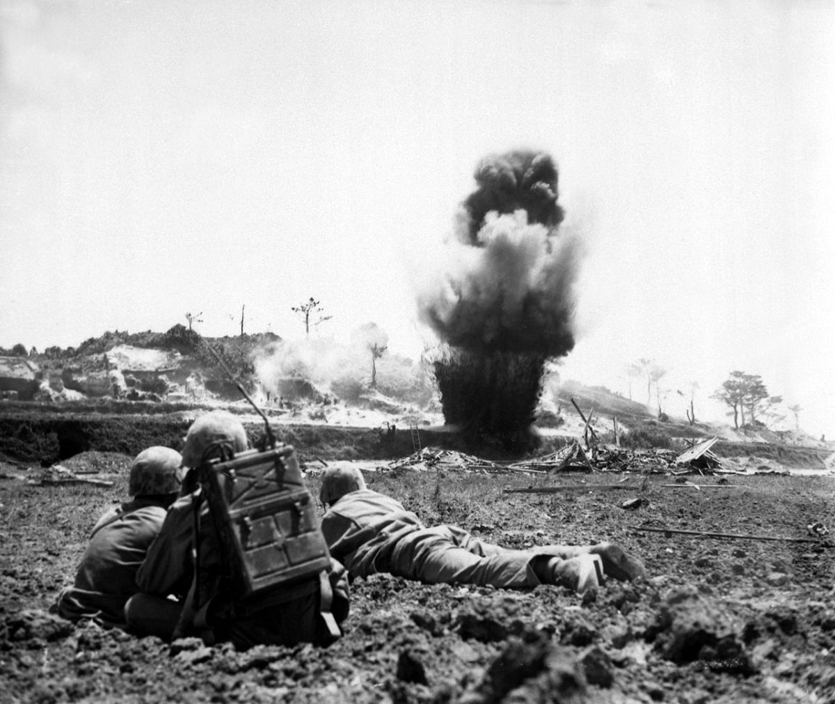 A 6th Marine Division demolition crew watches explosive charges detonate and destroy a Japanese cave, May 1945.