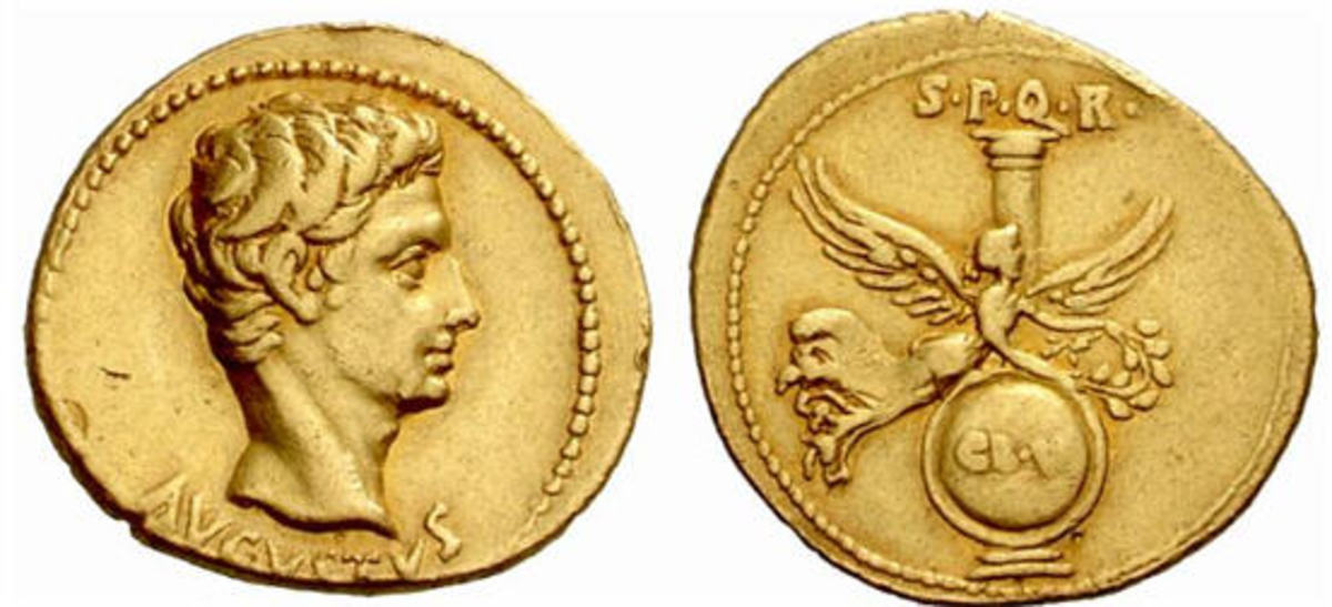 Bare head of Emperor Augustus on the left and Victory with her wings spread on the right, at the back is a column and a shield below.