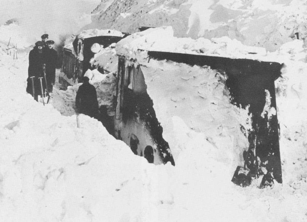 A sorry-looking snow plough and locomotive stuck in a drift, waiting to be pulled free