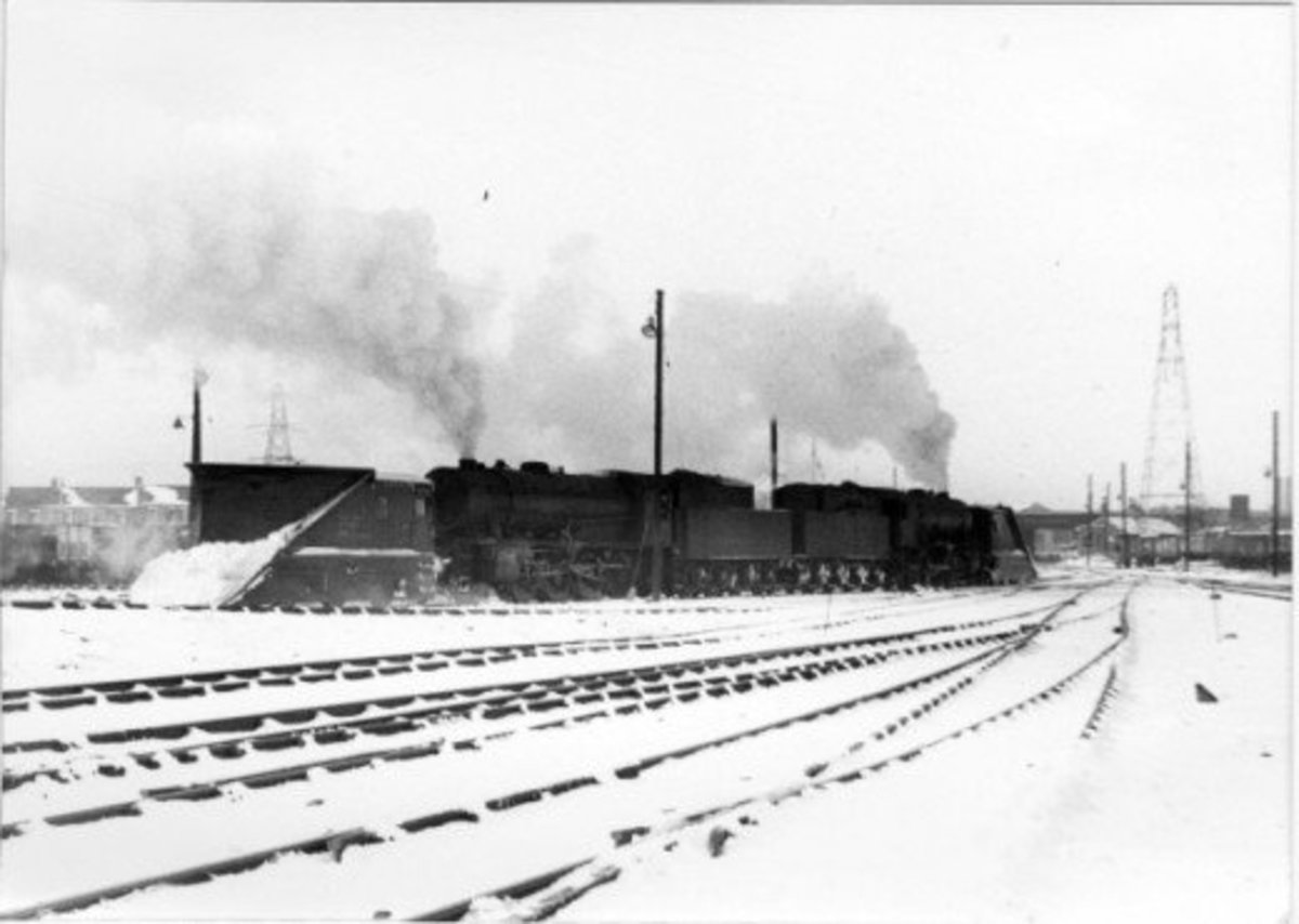 A pair of Austerity ex-WD 2-8-0 locomotives stand back-to-back with snow ploughs at either end, waiting at York for a call-out