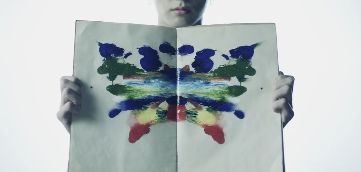 Jungkook opening the book with colorful stains.