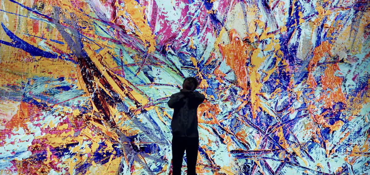Jimin dancing in front of the colorful painting.