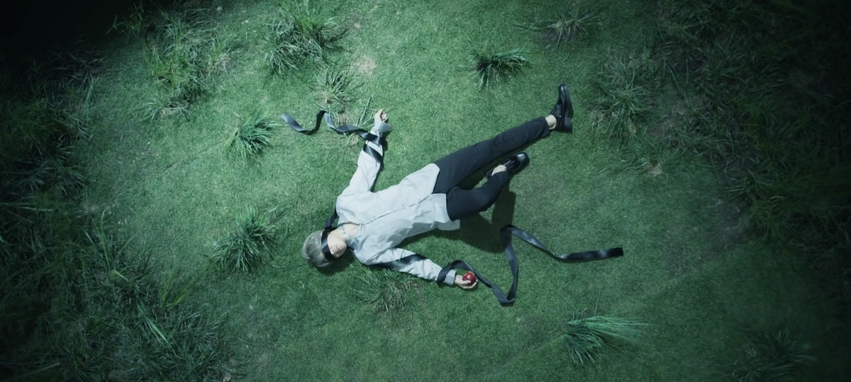 Jimin lying on the ground with an apple and blindfold.