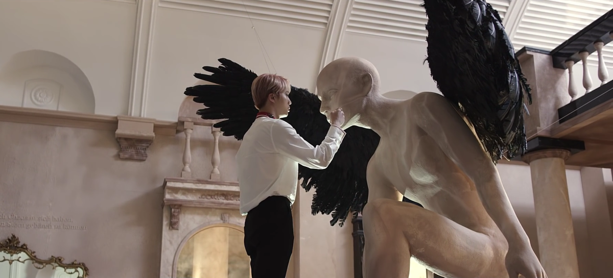 Jin approaching the statue with wings.