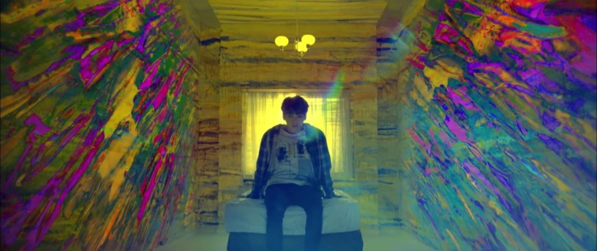 Jungkook inside of a room with colorful smears on the walls.