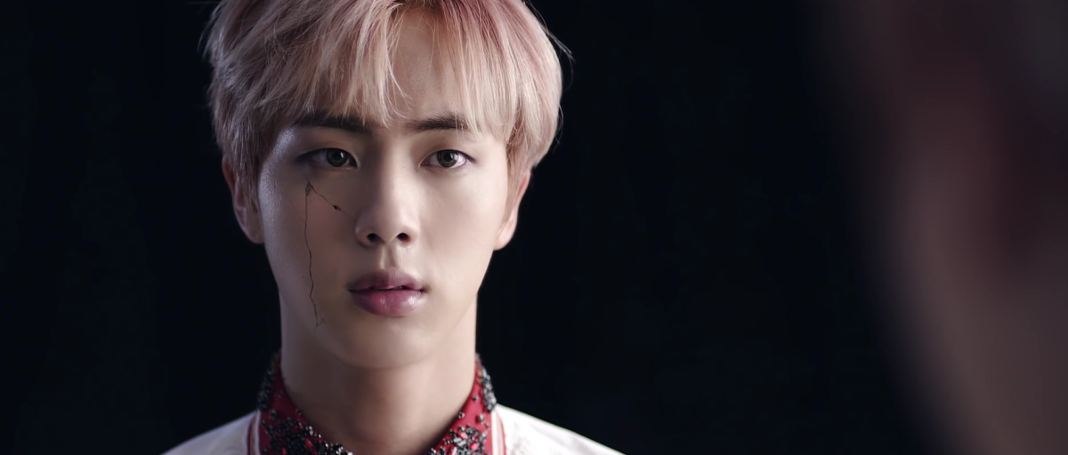 Jin's face starts to crack.