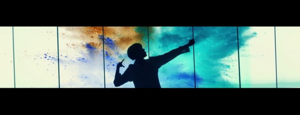 J-Hope firing an imaginary arrow with colors spreading behind him.