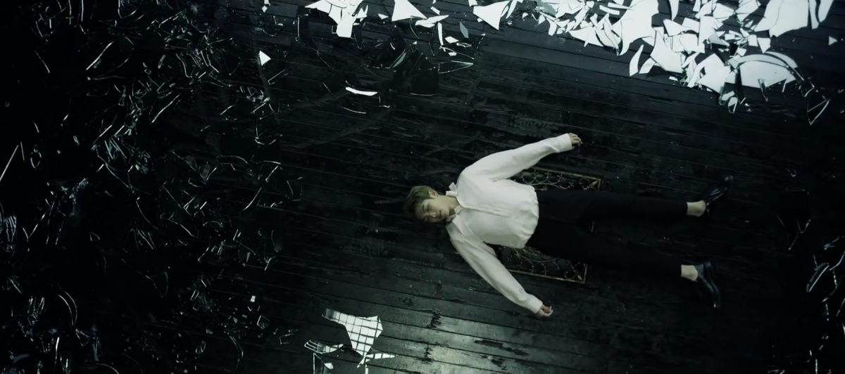 RM lying on the ground surrounded by broken glass shards.