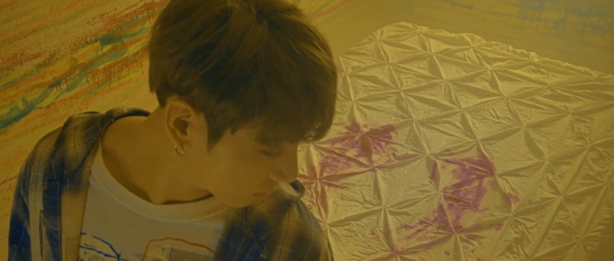 Two stains on the mattress behind Jungkook in the form of small wings.