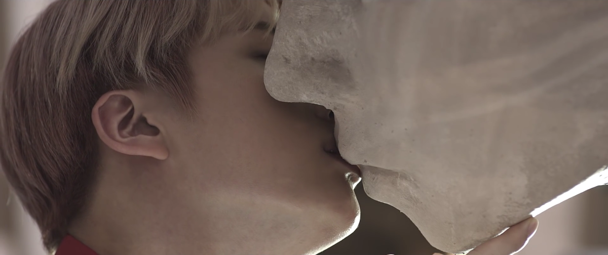 Jin kissing the statue with wings.