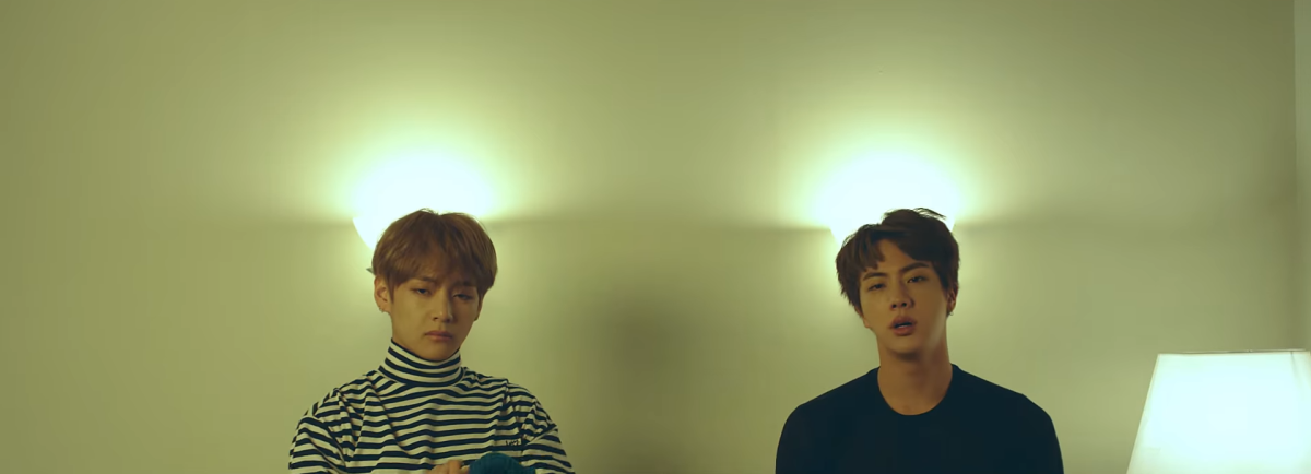 "V and Jin taking off their sweaters in ""Spring Day""."