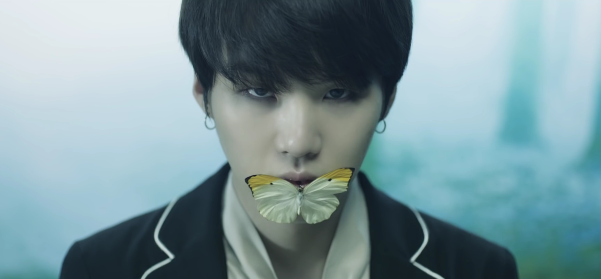 Suga with an orange-tip butterfly on his mouth.