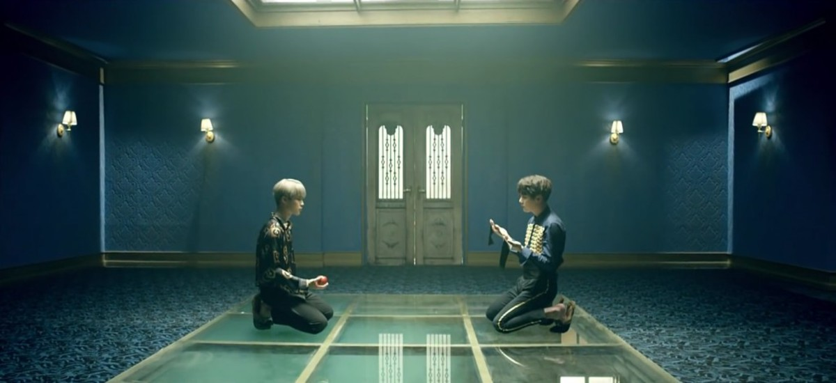 Jimin and Suga kneeling down on the floor, holding an apple and a blindfold.