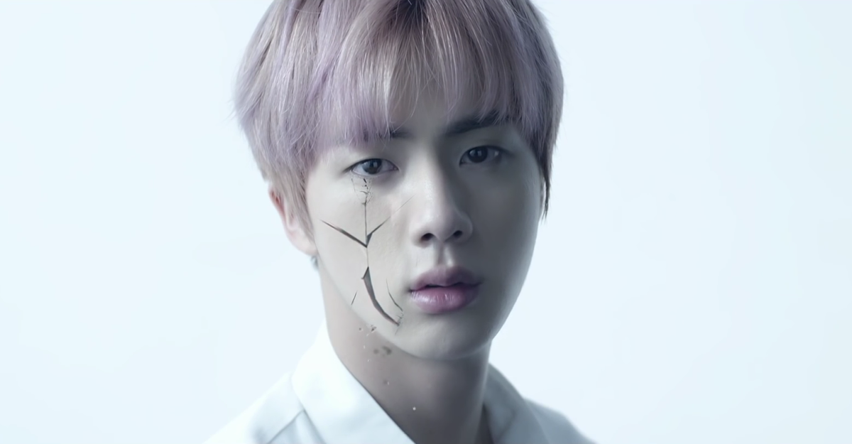 Jin's face starts cracking.
