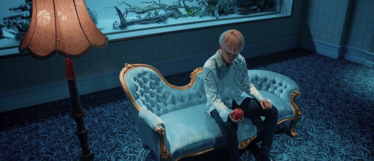 Jimin alone with an apple in his hand.