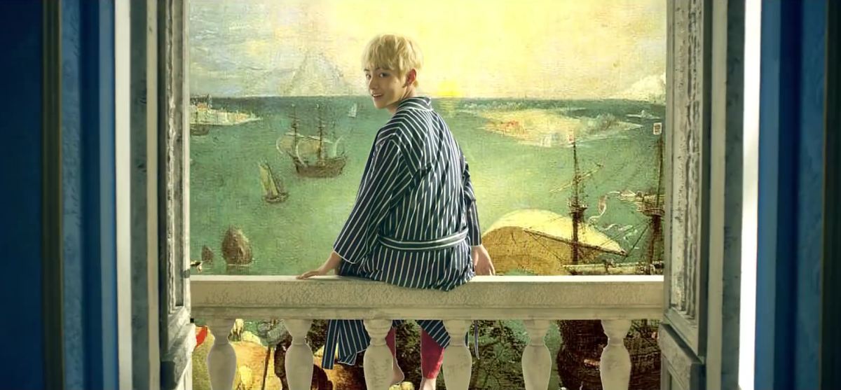 "V sitting on the balcony with the painting ""Landscape with the Fall of Icarus"" behind him."