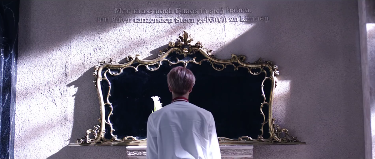 Jin in front of the mirror. Above we can see Nietzsche's quote.
