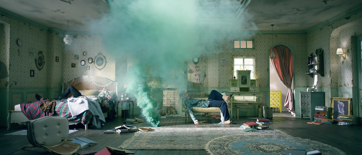 Jungkook and Rapmon lying in a room full of smoke completely paralyzed and hypnotized.
